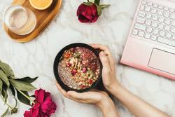 Hands holding smoothie bowl with laptop, peonies and water