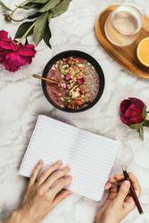 Hands holding smoothie bowl with notebook, peonies and water