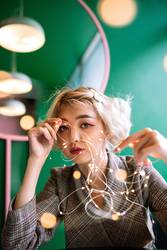 Blond asian young woman with fairy string lights