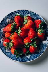 Fresh ripe strawberries in a blue and white plate