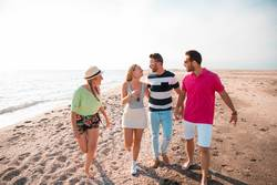Group of happy young people walking at the beach.