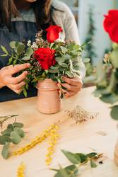 Woman florist makes a red rose bouquet on wooden table