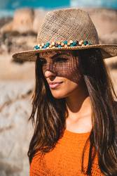 Woman hides her face from the sun under a straw hat