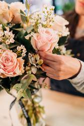 Woman florist makes a pink roses bouquet on wooden table