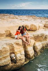 Two young women enjoying the views of the sea from a cliff