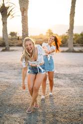 Two cheerful women played on the beach at the sunset time