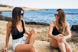 Two young women sitting on the seashore enjoying the summer