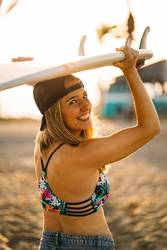 Smiling blonde girl holding over her head a surfboard at dusk