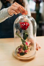 Florist making the eternal roses in the flask glass. Preserved
