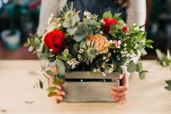 Woman florist makes flowers bouquet in wooden box on a table