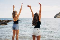 two young woman friends with raised hands, looking at sea