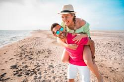 Handsome and happy man carrying his smiling girlfriend on beach.