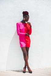 Attractive black woman wearing pink dress on white background