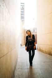 Smiling woman walking down a narrow corridor with black dress