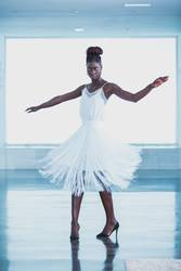 Attractive black woman wearing white fringed dress dancing