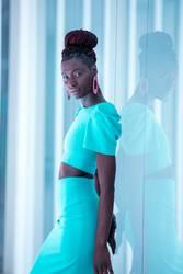 Attractive black woman wearing turquoise dress walks the runway