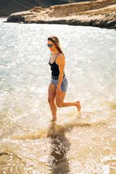 Pretty young woman walking on the beach during summer holiday