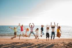 Group of happy young people jumping at the beach