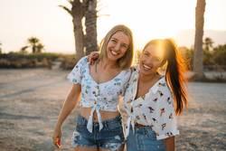 Two beautiful and smiling women enjoying on the beach