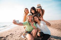 People making a selfie at the beach in a summer party.