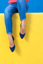 Closeup view of woman heels on a yellow wall