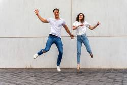 Happy couple in love jumping against grey wall.