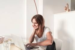 Adult woman working with laptop at home