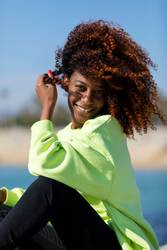 Side view of a beautiful curly afro woman sitting on breakwater