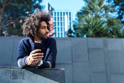 Portrait of handsome afro man using his phone