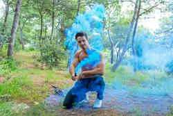 Young bare man in colored smoke outdoors in the forest