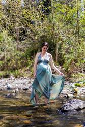Pregnant girl posing near the river wearing a green dress.