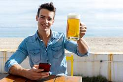 young man sitting on a beach club holding beer