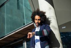 Young handsome man with afro hair Checking the time