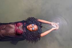 Beauty young African American woman floating in a pool of water