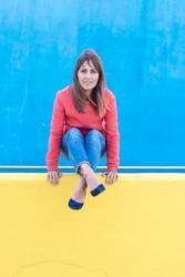 Woman in jeans enjoying on a yellow wall while looking camera