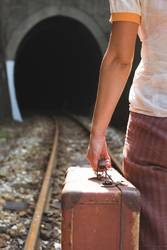 Woman and vintage suitcase on railway road and tunnel