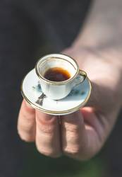 Hand hold very small cup of coffee.