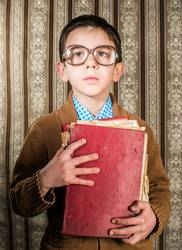 Child with glasses hold red vintage book