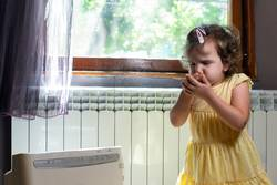 Little girl in a dusty room. Air purifier and coughing kid.