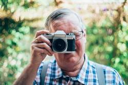 älterer Hippie-Mann mit einer alten Weinlesekamera