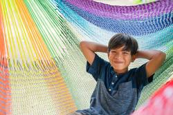 The little boy sitting at the hammock and he so happy