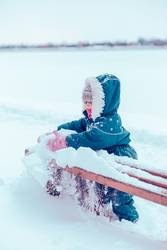 Little girl enjoying winter removing snow from a bench