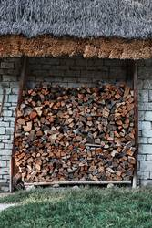 Logs of firewood stored under the stone shed