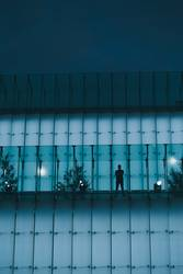 Man standing on backlit glass construction in a city center