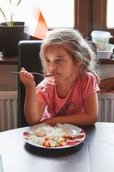 Child having a dinner at home