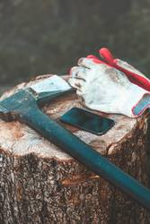 Mobile phone and tools, axe, work gloves on tree trunk