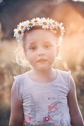 Little girl wearing a coronet of wild flowers on her head