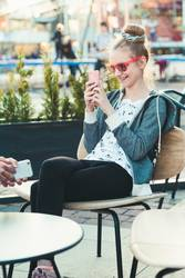 Teenage girl using smartphone sitting in center of town