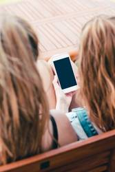 Young women using mobile phones watching music clip