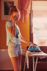 Young woman is ironing her clothes and talking on a smartphone